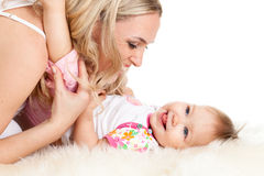 Loving mother embraces her baby girl. Loving mother playing her child;  child is lying on sheepskin Stock Image