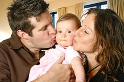 Loving mother and father kissing their baby girl. In indoor home setting Stock Image