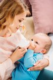 Loving mother feeding her little child. With baby bottle at home stock images