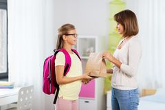 Loving mother giving daughter school lunch at home stock images