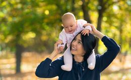 Loving mother giving her baby girl a ride. stock image