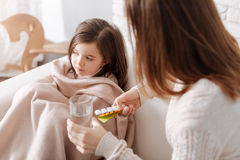 Loving mother giving pills to her ill daughter Royalty Free Stock Image