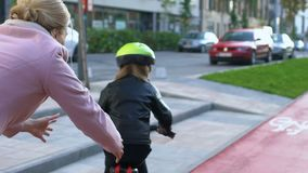Loving mother helping daughter learning to ride bicycle outdoors, connection
