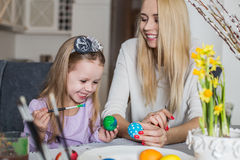 Loving mother and her daughter painting easter eggs Stock Images