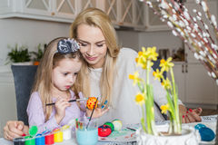 Loving mother and her daughter painting easter eggs. Cozy home atmosphere. Easter Royalty Free Stock Photography