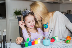 Loving mother and her daughter painting easter eggs Royalty Free Stock Photos