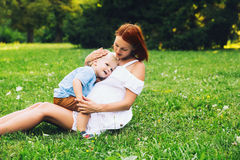 Loving mother and her son on nature. Pregnant women with toddler kid outdoors. Mother and her son on nature in summer park. Little child boy hugging mother, who Stock Images