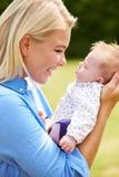 Loving Mother Holding Baby Daughter In Garden Stock Image