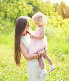 Loving mother holding on hands child hugging in summer stock photo