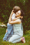 Loving mother hugging her son. Loving mother hugging her attractive young son on the cheek. Toned image royalty free stock photography