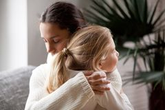 Loving mother hugging little girl, moms love and adoption concep. Loving mother hugging cute little girl, young women embracing adopted child holding tight royalty free stock image