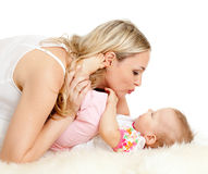 Loving mother kisses her child on sheepskin. Loving mother kisses her child;  child is lying on sheepskin Royalty Free Stock Photo