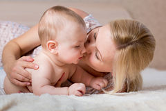 Loving mother kissing her baby boy Stock Photo