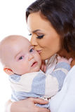 Loving mother kissing her small baby Stock Photos