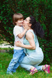 Loving mother kissing her son. Loving mother kissing her attractive young son on the cheek. Toned image Stock Photo