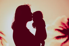 Loving mother and kissing little baby play at sunset. Beach Stock Photos
