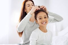 Loving mother making a hairdo for her daughter. Happy childhood. Pretty exuberant curly-haired girl smiling and her mother standing behind her and making a Stock Photo