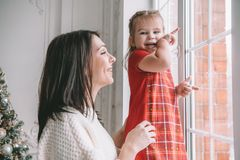 Loving mother playing with her baby girl looking at the window royalty free stock images