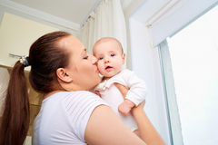 Loving mother playing with her baby on a window. stock image
