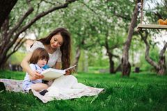 Loving mother reading book to toddler son outdoor on picnic in spring or summer park. Happy family and mothers day. Concept stock image
