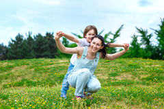 Loving mother rolls on a back of small son in park. Laughing mum rolls on a back of the small son in park Stock Images