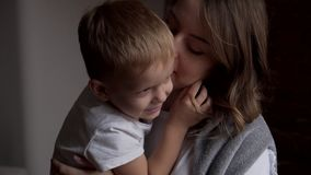Loving mother and son. Happy mother embracing and kissing her little son at home stock video footage