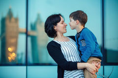 Loving mother and son hugging outdoors. In city stock image