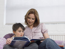 Loving Mother And Son Reading Book On Bed Stock Image