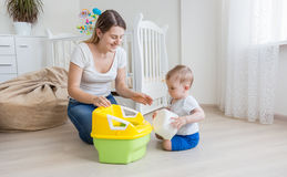 Loving mother teaching her baby boy how to use chamber pot. LYoung oving mother teaching her baby boy how to use chamber pot stock image