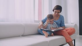 Loving mother teaching her son to read holding book speaking on couch at home. Loving mother teaching her son to read holding book speaking on couch at home stock footage