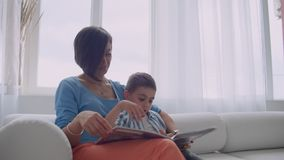 Loving mother teaching her son to read holding book speaking on couch at home. Loving mother teaching her son to read holding book speaking on couch at home stock video footage