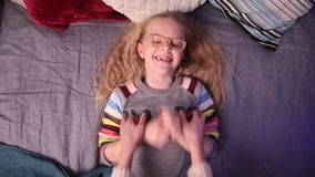 Loving mother tickling her little girl on the bed. Top view of little daughter laughing while her mother is tickling her on the bed. Mom with a child fool around stock video footage