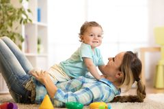Loving mother tickling her little kid on carpet at home. Loving mom tickling her little baby kid on carpet at home Stock Images