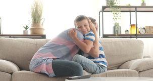 Loving mother embracing her son at home. Loving mother tightly embracing her son on sofa at home stock video