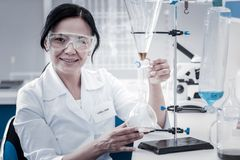 Positive minded chemist smiling cheerfully while conducting experiment. Loving my job. Selective focus on a beautiful mature lady wearing a labcoat and safety royalty free stock images