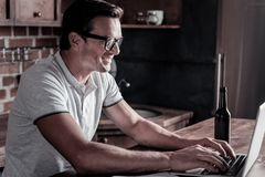 Educated gentleman working on laptop at home. Loving my job. Side view on an adult man wearing glasses smiling while typing on a laptop and relaxing with a Royalty Free Stock Photography