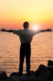 Loving nature. Businessman is standing near the sea at sunrise Royalty Free Stock Image
