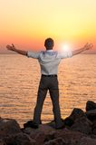 Loving nature. Businessman is standing near the sea at sunrise Royalty Free Stock Photo