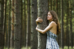 Loving Nature. A Young Woman is Showing a Natural Love by Embracing a Forest Tree Royalty Free Stock Photography