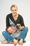 Loving the new pet Pug. Young woman with her son getting to know the new Pug they rescued from the animal shelter Stock Photos