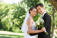 Loving newly wed couple in garden Royalty Free Stock Photography