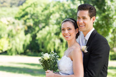 Loving newly wed couple looking away in park Royalty Free Stock Photos