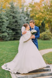 Loving newlywed couple walking in sunny park at alley. Charming bride holding her bridal bouquet Royalty Free Stock Photos