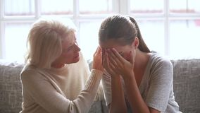 Loving old mother sympathizing consoling upset crying young daughter. Loving sad old mother sympathizing consoling upset depressed young daughter crying stock video footage
