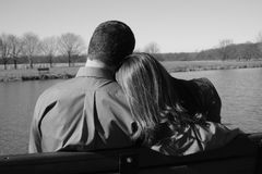 Loving pair enjoying each other's company. Young couple on park bench Stock Images