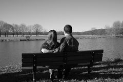 Loving pair enjoying each other's company. Young couple on park bench Royalty Free Stock Image