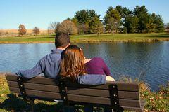 Loving pair enjoying each other's company. Young couple on park bench Royalty Free Stock Photos
