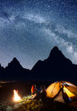 Loving pair - guy and girl sitting face to face in front tent near bonfire under shines starry sky at night Royalty Free Stock Image