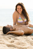 Loving pair laying on sand beach Royalty Free Stock Photography