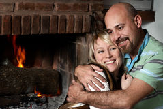 Loving pair near a fireplace in winter evening Stock Photography